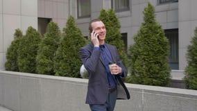 Un hombre de negocios joven que camina abajo de la calle y comunica feliz en la llamada de tel?fono