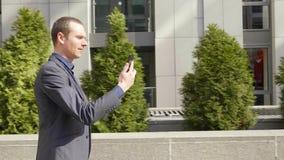 Un hombre de negocios joven que camina abajo de la calle y comunica feliz en la llamada video