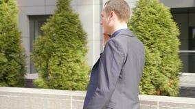 Un hombre de negocios joven que camina abajo de la calle y de las negociaciones sobre la llamada de teléfono