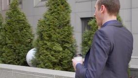 Un hombre de negocios joven que camina abajo de la calle y de las negociaciones sobre la llamada de tel?fono