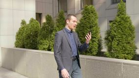 Un hombre de negocios joven que camina abajo de la calle y de las negociaciones sobre la llamada video