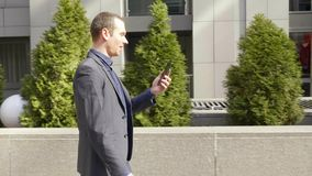 Un hombre de negocios joven que camina abajo de la calle y de las negociaciones sobre la llamada video metrajes