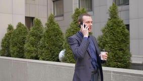 Un hombre de negocios joven que camina abajo de la calle y lleva agresivamente una discusión sobre la llamada de teléfono