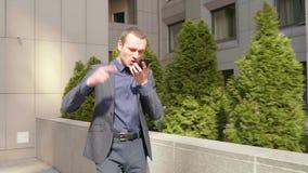Un hombre de negocios joven que camina abajo de la calle y lleva agresivamente una discusión sobre la llamada telefónica