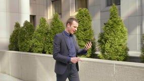 Un hombre de negocios joven que camina abajo de la calle y lleva agresivamente una discusión sobre la llamada video