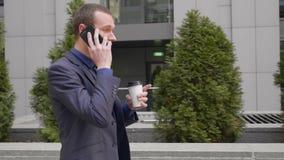 Un hombre de negocios joven que camina abajo de la calle y lleva agresivamente una discusi?n sobre la llamada de tel?fono