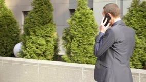 Un hombre de negocios joven que camina abajo de la calle y lleva agresivamente una discusi?n sobre la llamada telef?nica