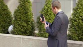 Un hombre de negocios joven que camina abajo de la calle y lleva agresivamente una discusi?n sobre la llamada video