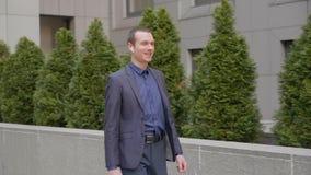 Un hombre de negocios joven que camina con los auriculares inalámbricos y comunica feliz en una llamada telefónica
