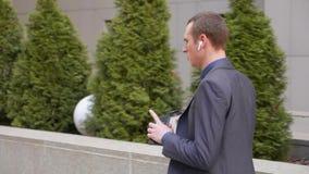 Un hombre de negocios joven que camina con los auriculares inalámbricos y lleva agresivamente una discusión sobre llamada telefón