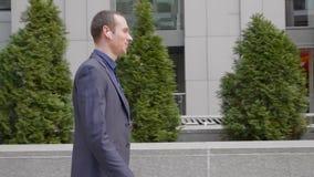 Un hombre de negocios joven que camina con los auriculares inal
