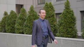 Un hombre de negocios joven que camina con los auriculares inal?mbricos y comunica feliz en una llamada telef?nica