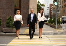 Un hombre de negocios joven que camina en la calle con sus secretarias Fotografía de archivo libre de regalías