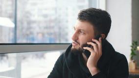 Un hombre de negocios joven que habla en el teléfono y que trabaja en un ordenador portátil en un café almacen de video