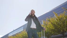 Un hombre de negocios joven que habla en una situación del smartphone cerca de oficina de negocios moderna con la maleta en el ai metrajes