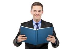 Un hombre de negocios joven que lee un libro Foto de archivo libre de regalías