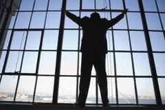 Un hombre de negocios joven que se coloca en y que mira hacia fuera TA Imagen de archivo libre de regalías