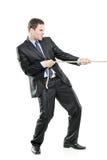 Un hombre de negocios joven que tira de una cuerda Imagenes de archivo