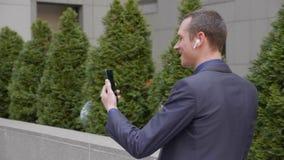 Un hombre de negocios joven viene con los auriculares inalámbricos en sus oídos y feliz las negociaciones sobre una llamada vid