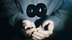 Un hombre de negocios levanta el icono del infinito de las manos metrajes
