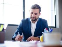 Un hombre de negocios de los jóvenes firma documentos en su escritorio fotografía de archivo