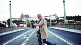 Un hombre de negocios maduro con el bolso que cruza un camino en la ciudad de Praga metrajes