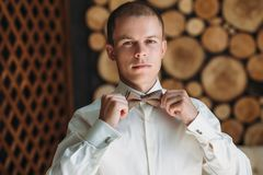 Un hombre de negocios masculino joven está consiguiendo se vistió para el trabajo Un individuo rubio en una camisa blanca está in Imágenes de archivo libres de regalías