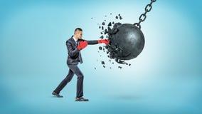 Un hombre de negocios minúsculo en guantes de boxeo rojos rompe una bola arruinadora de balanceo grande en pequeños pedazos foto de archivo