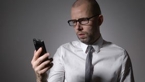 Un hombre de negocios o un encargado de mediana edad en los vidrios que sostienen un smartphone en las manos y las impresiones en metrajes