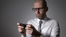 Un hombre de negocios o un encargado de mediana edad en los vidrios que sostienen un smartphone en las manos y las impresiones en almacen de metraje de vídeo