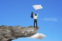 Un hombre de negocios que anima en el acantilado que agita la bandera en blanco con el cielo Imágenes de archivo libres de regalías