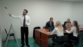 Un hombre de negocios que discute una carta de tirón en un tablero blanco en una sala de reunión al equipo de trabajo mientras qu almacen de metraje de vídeo