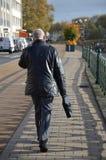 Un hombre de negocios que habla en el teléfono mientras que camina afuera Foto de archivo libre de regalías