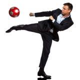 Un hombre de negocios que juega golpeando el balón de fútbol con el pie Fotografía de archivo