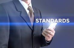 Un hombre de negocios que lleva a cabo una muestra blanca con los estándares del mensaje foto de archivo