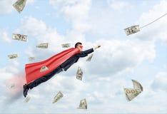 Un hombre de negocios que lleva un vuelo rojo del cabo del super héroe a través de las nubes que siguen un billete de dólar Foto de archivo libre de regalías