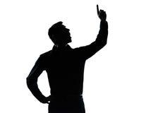 Un hombre de negocios que señala encima de silueta sorprendida Fotografía de archivo libre de regalías
