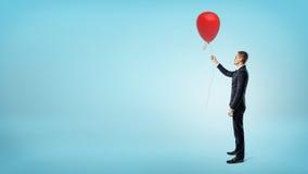 Un hombre de negocios que se coloca en vista lateral sobre fondo azul y que sostiene un balón de aire rojo Fotos de archivo