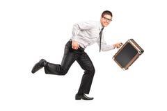 Un hombre de negocios que se ejecuta con una cartera Imágenes de archivo libres de regalías