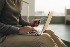 Un hombre de negocios que se sienta con el ordenador portátil en sus rodillas y mano toma la tarjeta imagen de archivo libre de regalías