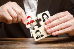 Un hombre de negocios recoge los rompecabezas que simbolizan a un equipo de empleados El concepto de la organización del equipo y imagen de archivo libre de regalías