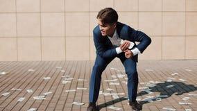 Un hombre de negocios recoge rápidamente el dinero que dispersó abajo de la calle Lluvia del dinero Avaricia humana El concepto d almacen de metraje de vídeo