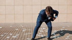 Un hombre de negocios recoge rápidamente el dinero que dispersó abajo de la calle Lluvia del dinero Avaricia humana El concepto d almacen de video