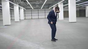 Un hombre de negocios salta mientras que lleva las auriculares de VR en una oficina almacen de video