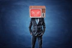 Un hombre de negocios se coloca con las manos en sus bolsillos y lleva una caja de la TV en su cabeza con una pantalla roja que m Foto de archivo libre de regalías