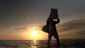 Un hombre de negocios sin los pantalones en el mar aumenta entusiasta un ordenador portátil y feliz danzas metrajes