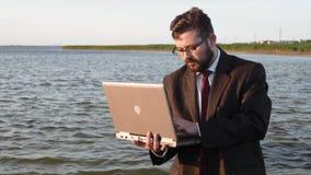 Un hombre de negocios sin los pantalones pero con un ordenador portátil se coloca en el agua almacen de video