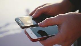 Un hombre de negocios, sosteniendo dos teléfonos móviles en sus manos, manosea sus fingeres con los dedos en el monitor 1920x1080 almacen de video