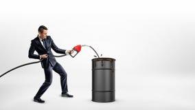 Un hombre de negocios sostiene una boca de gas y sobrellena un barril negro con aceite Imagen de archivo