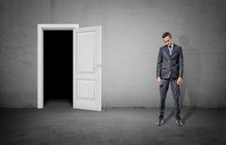 Un hombre de negocios triste con el suyo punto bajo de la cabeza se coloca cerca de un marco de puerta que muestra oscuridad comp fotografía de archivo